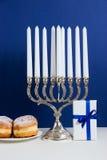 Celebración de Jánuca Palmatoria con los anillos de espuma fritos, regalo, en el fondo blanco y azul Fotos de archivo libres de regalías