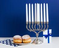 Celebración de Jánuca Palmatoria con los anillos de espuma fritos, regalo, en el fondo blanco y azul Imagen de archivo