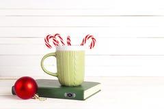 Celebración de la Navidad con el bastón y la taza de caramelo en el libro en de madera Foto de archivo