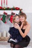Celebración de la Navidad o del Año Nuevo La hija feliz abraza la localización de la madre cerca de una chimenea de la Navidad bl Fotografía de archivo libre de regalías