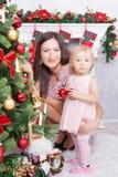 Celebración de la Navidad o del Año Nuevo La madre feliz abraza a la hija cerca de una chimenea de la Navidad blanca Fotos de archivo libres de regalías