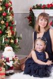 Celebración de la Navidad o del Año Nuevo La madre feliz con su hija se sienta cerca de un árbol de navidad Imagen de archivo libre de regalías