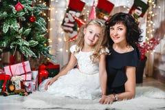 Celebración de la Navidad o del Año Nuevo La madre feliz con su hija se sienta cerca de una chimenea blanca al lado de un árbol d Fotos de archivo