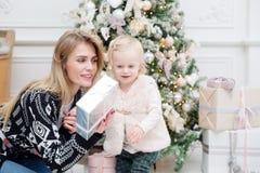 Celebración de la Navidad o del Año Nuevo La mamá feliz da el regalo de la hija adornado con la cinta Imagenes de archivo