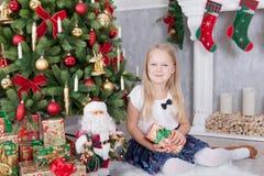 Celebración de la Navidad o del Año Nuevo Muchacha hermosa joven en las manos que sostienen el regalo de la Navidad que se sienta Fotos de archivo