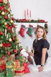 Celebración de la Navidad o del Año Nuevo Mujer feliz con un vidrio de champán que se sienta cerca del árbol de navidad con los r Imagen de archivo