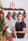 Celebración de la Navidad o del Año Nuevo Mujer feliz con un vidrio de champán que se sienta cerca del árbol de navidad con los r Imagen de archivo libre de regalías