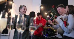 Celebración del Año Nuevo El hombre vierte el champán en los vidrios mientras que danza de la gente joven en el fondo antes de un metrajes