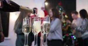 Celebración del Año Nuevo El hombre vierte el champán en los vidrios mientras que danza de la gente joven en el fondo antes de un almacen de video