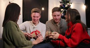 Celebración del Año Nuevo 4K Dos pares celebran antes de un árbol de navidad e intercambian sus presentes por uno a almacen de video