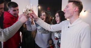 Celebración del Año Nuevo 4K Sonido metálico joven de tres pares sus vidrios que se colocan antes de un árbol de navidad almacen de video