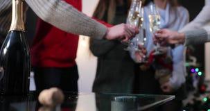 Celebración del Año Nuevo La gente baila en el fondo mientras que la cámara se centra en las flautas de champán almacen de metraje de vídeo