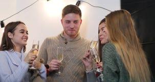 Celebración del Año Nuevo La gente bonita charla el champán de consumición en el cuarto antes de un árbol de navidad metrajes