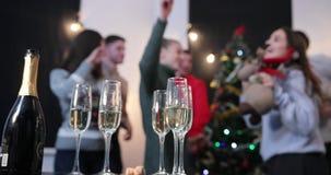Celebración del Año Nuevo La gente toma las flautas de champán de la tabla de cena mientras que ella baila antes de un árbol de n almacen de video