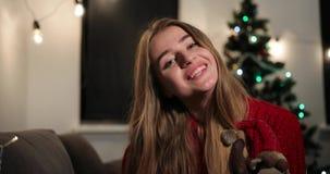 Celebración del Año Nuevo La mujer encantadora en suéter rojo se sienta en el sofá antes de un árbol de navidad, de sonrisas y de almacen de metraje de vídeo