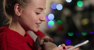 Celebración del Año Nuevo La mujer joven encantadora en suéter rojo se sienta en el sofá antes de un árbol de navidad y charla co almacen de video