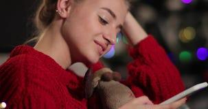 Celebración del Año Nuevo La mujer joven encantadora en suéter rojo se sienta en el sofá antes de un árbol de navidad y charla co almacen de metraje de vídeo