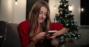 Celebración del Año Nuevo La mujer joven encantadora en suéter rojo se sienta en el sofá antes de un árbol de navidad y charla co metrajes