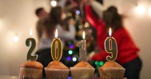 Celebración del Año Nuevo Magdalenas con las velas en soporte de los números 2019 en la tabla antes de celebrar alegre de la comp almacen de video