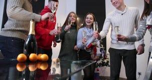 Celebración del Año Nuevo Muchachos y sonido metálico de las muchachas sus vidrios con el champán que se coloca en el cuarto con  almacen de video