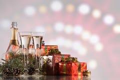 Celebración del Año Nuevo y de la Navidad Champán, dos copas de vino, fuegos artificiales y regalos Foto de archivo