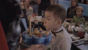 Celebración del cumpleaños Velas que soplan del niño en la torta almacen de video