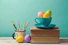 Celebración del día de fiesta de Pascua con los huevos pintados hechos a mano en taza de café Fotos de archivo