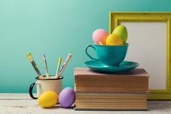 Celebración del día de fiesta de Pascua con los huevos pintados hechos a mano en taza, libros y cepillos de café Lugar de trabajo Fotografía de archivo