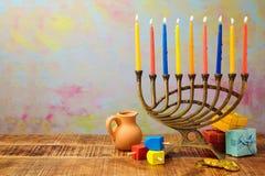Celebración judía de Jánuca del día de fiesta con el menorah, el dreidel, los regalos y el jarro del aceite Fotos de archivo libres de regalías