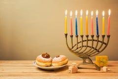 Celebración judía de Jánuca del día de fiesta con el menorah y el sufganiyot Imágenes de archivo libres de regalías