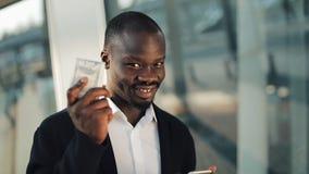 Celebración que anima del hombre de negocios afroamericano feliz mirando el teléfono celular y sosteniendo una gran cantidad de d metrajes