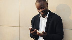 Celebración que anima del hombre de negocios afroamericano feliz mirando el teléfono celular y sosteniendo una gran cantidad de d almacen de video