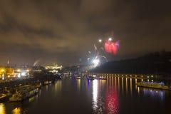 Celebración roja y amarilla asombrosa del fuego artificial del Año Nuevo 2015 en Praga con la ciudad histórica en el fondo Imagen de archivo