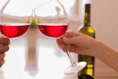 Celebración tintineando los vidrios de vino rojo imagenes de archivo