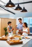 celebración Amigos que tienen partido de cena Consumición de la pizza, bebiendo Fotografía de archivo libre de regalías