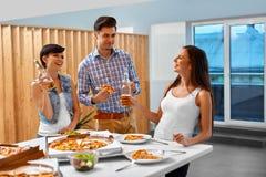 celebración Amigos que tienen partido de cena Consumición de la pizza, bebiendo Imagen de archivo libre de regalías