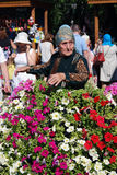 Celebración de Sabantui en Moscú Mujer mayor rodeada por las flores Imagen de archivo libre de regalías
