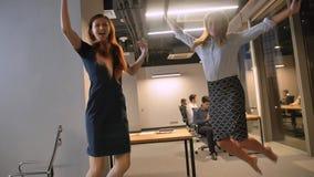 Celebraing för banhoppning för två businessladies lycklig framgång i den moderna Coworking mitten lager videofilmer