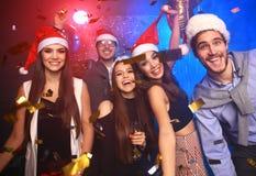 Celebrando Año Nuevo junto Grupo de gente joven hermosa en los sombreros de Papá Noel que lanzan confeti colorido, pareciendo fel Fotos de archivo libres de regalías