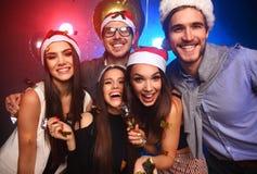 Celebrando Año Nuevo junto Grupo de gente joven hermosa en los sombreros de Papá Noel que lanzan confeti colorido, pareciendo fel Foto de archivo