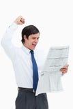 Celebrando al comerciante que tiene una mirada en las noticias Imagen de archivo libre de regalías