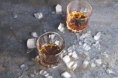 Celebrando alla barra Accoppi dei vetri con whiskey ed i pezzi di ghiaccio sulla tavola grigia fotografie stock