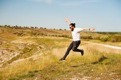 Celebrando concepto del éxito al aire libre - el hombre moderno de la diversión que saltaba con los brazos aumentó con la energía foto de archivo