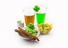 Celebrando el día del ` s de St Patrick - dos vidrios de verde sin filtro de la cerveza deliciosa con bocados y microprocesadores imagen de archivo