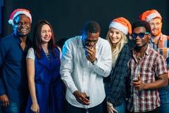 Celebrando nuovo anno insieme Gruppo di bei giovani in cappelli di Santa fotografie stock libere da diritti