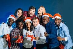 Celebrando nuovo anno insieme Gruppo di bei giovani in cappelli di Santa fotografia stock libera da diritti