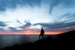 Celebrando o meditando al hombre que mira el océano de la puesta del sol fotos de archivo libres de regalías