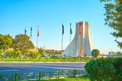 The celebranion at Azadi square in Tehran, Iran. Azadi Tower is surrounded by festival flags containing the names of Imams and muslim prays due to the Mourning stock photo