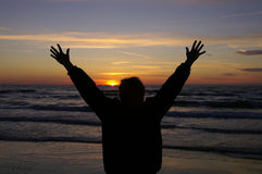 Celebrate. A person celebrates the sunset with open arms Stock Photography