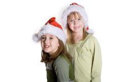 Celebrate. 2 sisters wearing santa hats Stock Images
